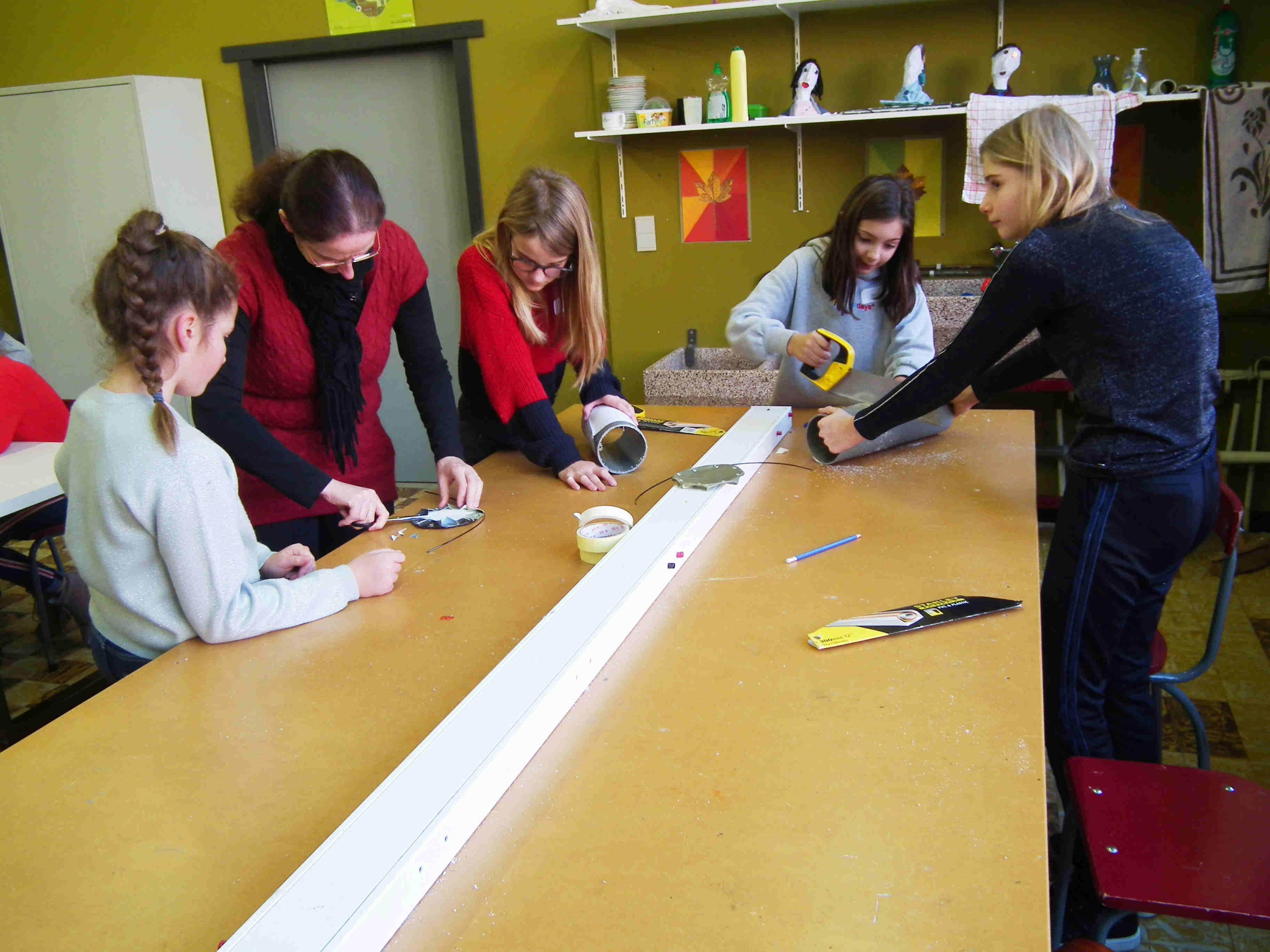 Nog een laatste helpende hand van de begeleidende leraar. Zeildoek en PVC-buis zijn klaar voor montage!